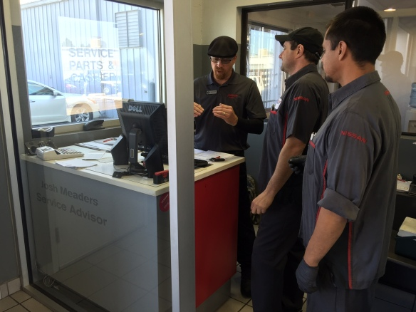 Service advisor Josh, touching base with a few of his team members before the day begins.  Communicating with customers and team members are at the core of this job opportunity.